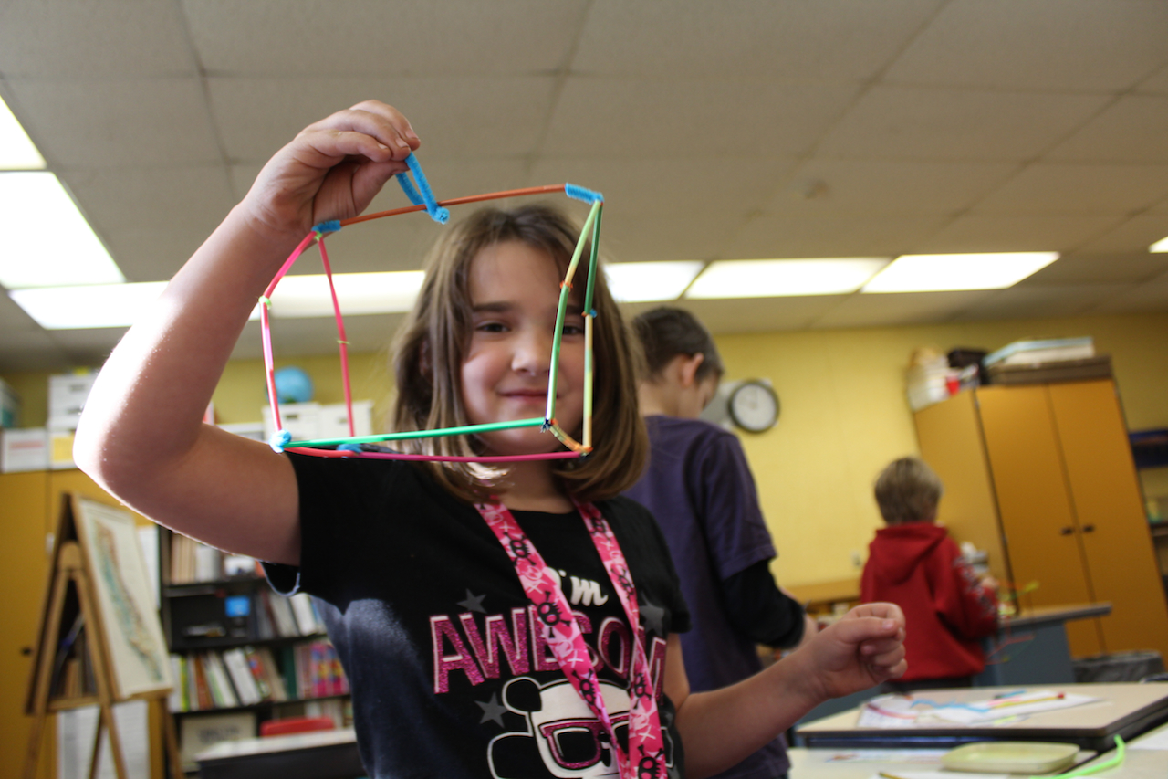A student displays a geometric figure she built with straws during a Common Core-based math lesson in her 3rd grade classroom.