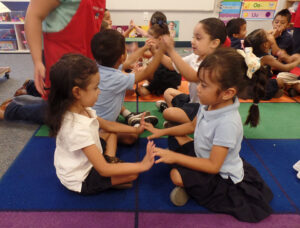 Head Start students Danna Vazquez Ramirez and Paulina Manriquez hold their hands together and form a bridge to talk about what they learned in a lesson about the human body during a Sobrato Early Academic Language, or SEAL, class in El Monte in October 2015.