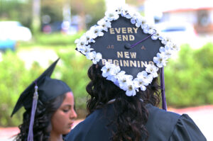 A student at from Santa Ana's Middle College High School graduation celebrates by decorating her motarboard with flowers and an inspirational message.